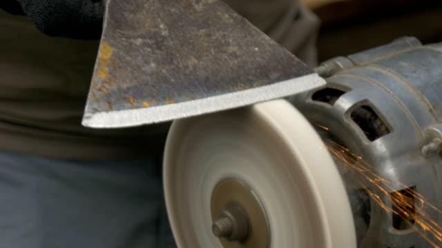 A man is sharpening a big ax on a makeshift machine. video