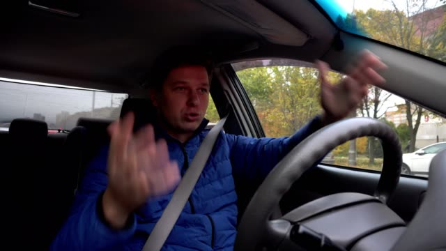 A man is shouting at the wheel of a car. video