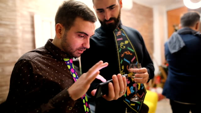 Man is showing something interesting and funny to his friend.Party concept funny neckties