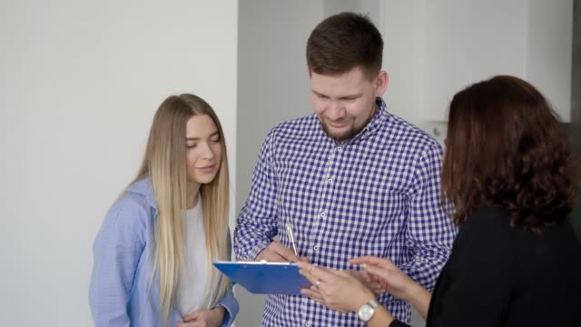 man is signing contract of a rent an apartment and realtor is giving him keys, his young wife is rejoicing man is signing contract of a rent an apartment and realtor is giving him keys, his young wife is rejoicing and hugging him house rental stock videos & royalty-free footage