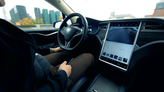 A man is sitting in a vehicle which is being automatically driven video
