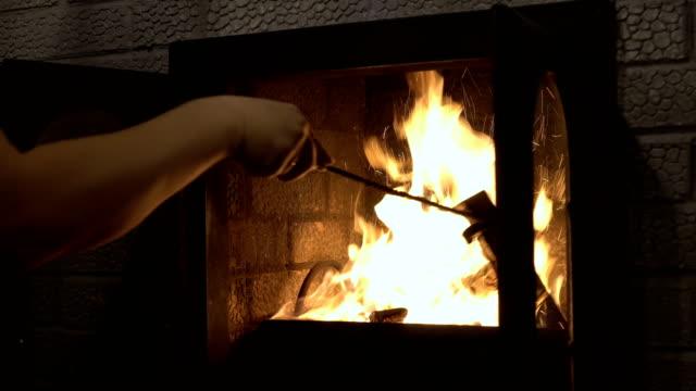 vídeos de stock e filmes b-roll de a man is stirring logs in a burning home fireplace. closeup. 4k - burned oven