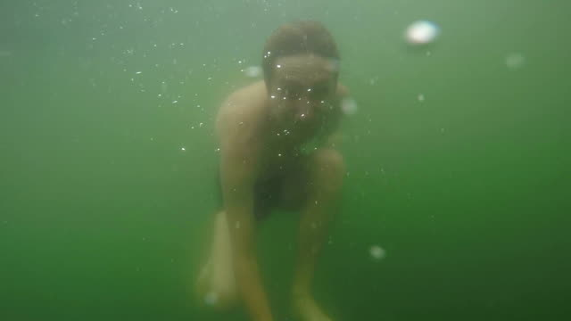 Man is swimming underwater in the lake. video
