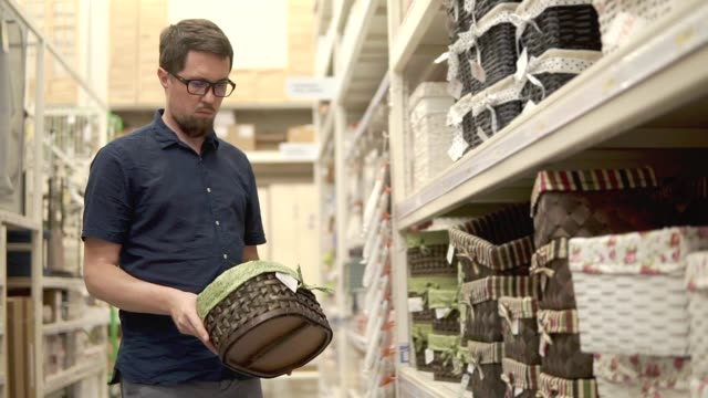 Man is taking different woven baskets from racks in a shop, choosing