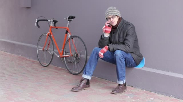 a man is talking on the phone near a bicycle - giuntura umana video stock e b–roll