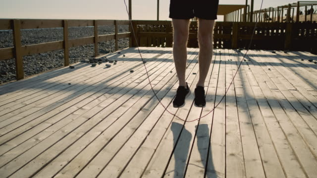 Man is training outdoors, using jumping rope, close-up of legs - video