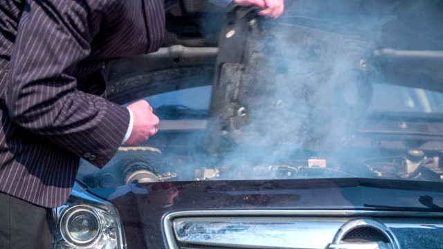 Man is trying to fix the car in the business clothes in the middle of a countryside, footage is taken  in slow motion. video