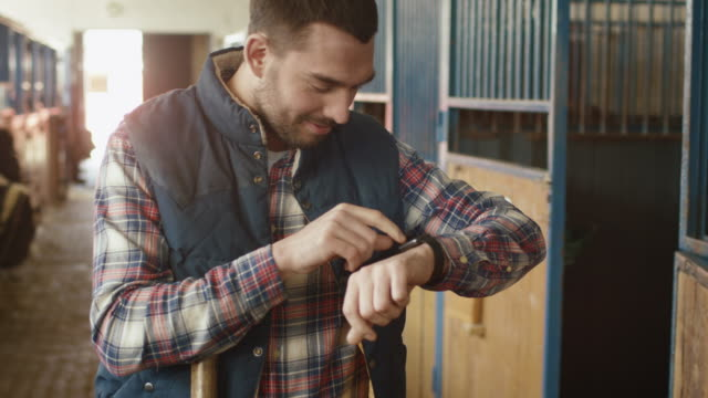 man is using a smart watch in stable. - computer indossabile video stock e b–roll