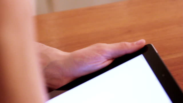 Man is using an ipad on a wooden table video
