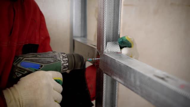 mann nutzt elektrischen schraubenzieher verdrehen schrauben in aluminiumkonstruktion bei reparatur im hause - schraube stock-videos und b-roll-filmmaterial