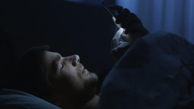 男はベッドで電話を使っています - スマホ ベッド点の映像素材/bロール