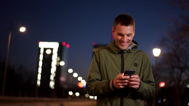 man använder smart telefon på natten - endast en man i 30 årsåldern bildbanksvideor och videomaterial från bakom kulisserna