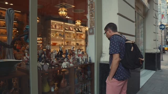 Man is viewing a showcase of souvenir store in old touristic city in summer day Male tourist is looking on a small statues on a shelf in gift shop. He is standing outdoors and watching through glass of window, in touristic center souvenir stock videos & royalty-free footage