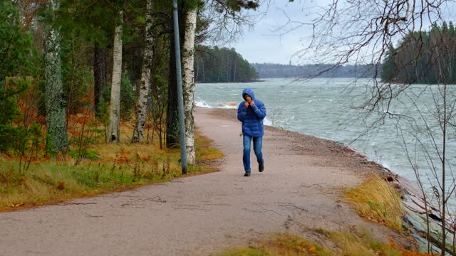 A man is walking against a strong gale force wind. A man is walking along the embankment against a strong stormwind. coastal feature stock videos & royalty-free footage