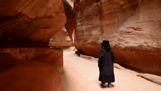 A man is walking on the path leading to Al Khazneh (The Treasury)in Petra, Jordan. A man is walking on the path leading to Al Khazneh (The Treasury). Amazing Path that passes between a beautiful canyon made up of red rocks in Petra, Jordan. treasury stock videos & royalty-free footage