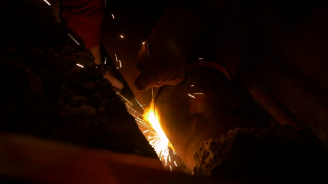 A man is welding two heating system pipes together video