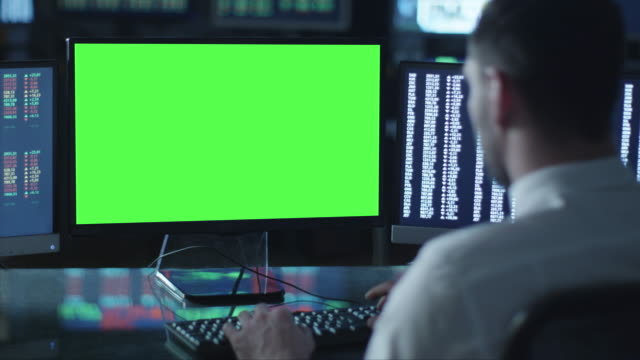 Man is working on a computer with mock-up green screen in a dark office filled with displays. video