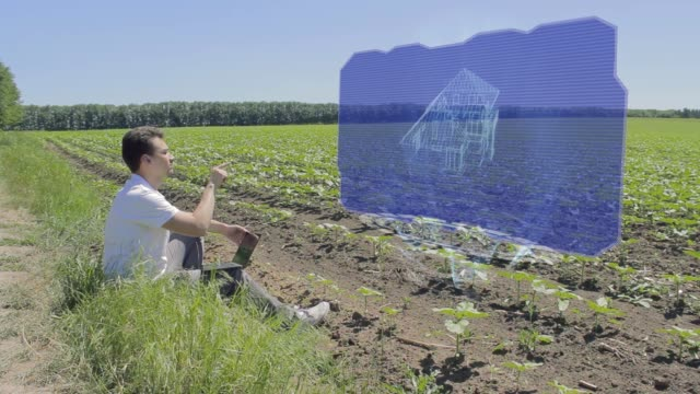 Man is working with 3D house on holographic display on the edge of the field