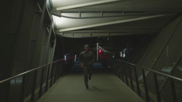 man jogging across bridge early morning or late at night - solo un uomo video stock e b–roll