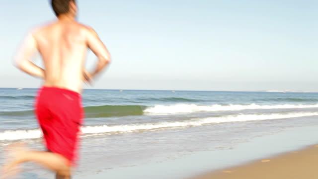Man Jogging Along Empty Beach video