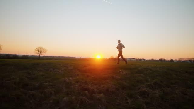 SLO MO WS TS Man jogging at sunset