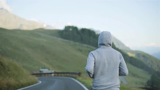 man jogga tillbaka på landsbygden bergsväg i naturen närbild slowmotion. hooded manlig figur köra följt i morgon hill lutning bakgrunden på lokala asfalterad väg i grå sportkläder och sneakers - jogging hill bildbanksvideor och videomaterial från bakom kulisserna