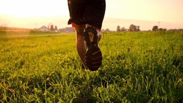 stockvideo's en b-roll-footage met slo mo man jogging in wet grass - menselijk been