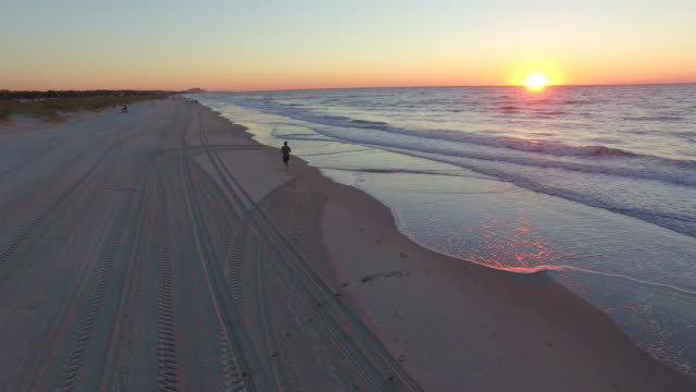 Man Jogging On Beach At Sunrise video