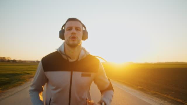 stockvideo's en b-roll-footage met slo mo ms ts td man joggen op de weg bij zonsondergang - medium filmcompositietype