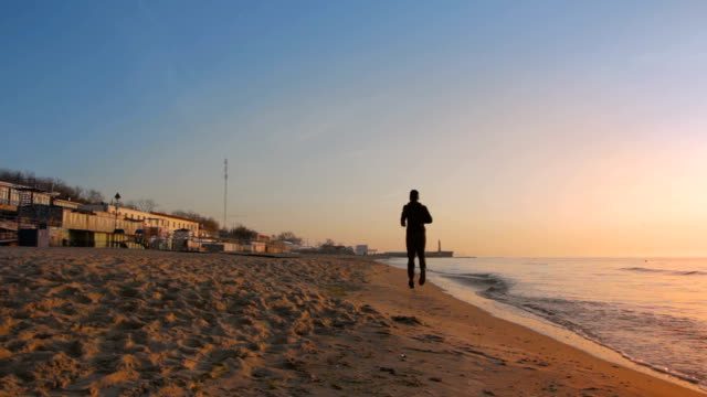 Man jogging on the beach during sunset at the sea shore Man jogging on the beach during sunset at the sea shore. Beautiful sunny but cold morning at the beach human back stock videos & royalty-free footage