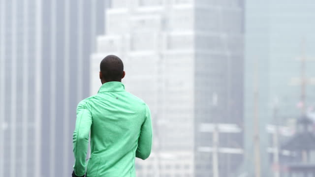 A man jogs away from the camera in front of skyscrapers in New York in the rain video