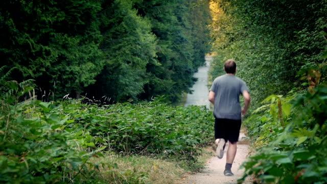 mann joggt auf staubigen schotterweg durch sonnenuntergang wald - vancouver kanada stock-videos und b-roll-filmmaterial