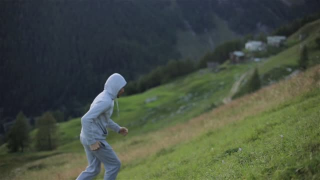 man jogs runs up mountain hill face close up slow motion. hooded runner jogger sprints with effort trains for marathon outdoors on grass in fresh air grey sportswear sneakers. sport healthy lifestyle - avvicinarsi video stock e b–roll