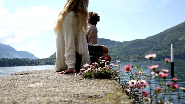 stockvideo's en b-roll-footage met man joins woman above lake - sober leven