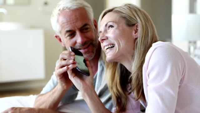 Man jokingly taking phone off partner talking video