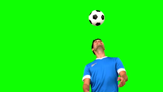 Man juggling a football with his head on green screen video