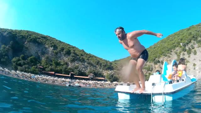 mann springt von tretboot - sprung wassersport stock-videos und b-roll-filmmaterial