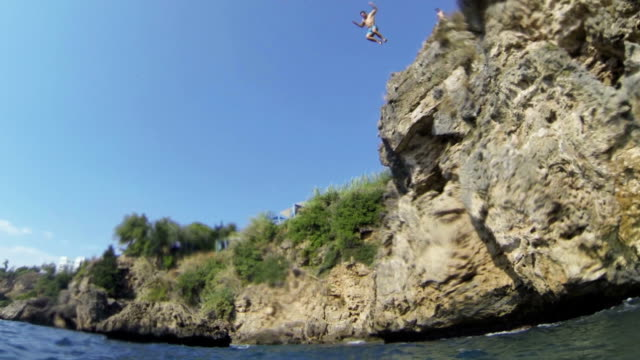 hd: man jumping into sea slow motion - cliffs stock videos & royalty-free footage