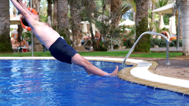 Man jumping into swimming pool in slow motion 180fps video