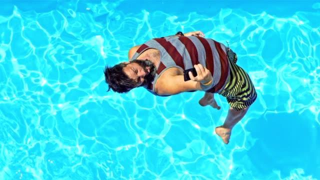 rallent cs uomo saltando in piscina e scattare foto - saltare video stock e b–roll