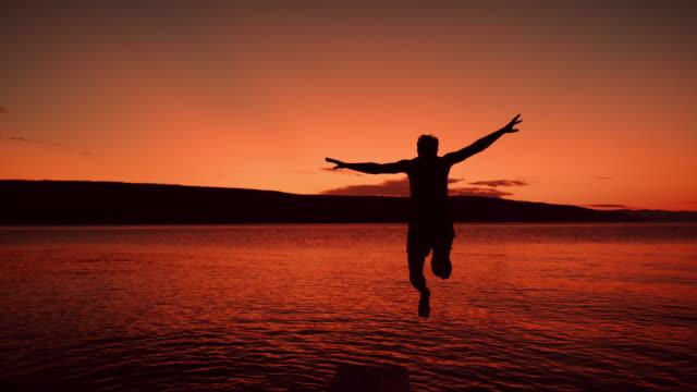 TIME WARP Man jumping into the sea at dusk