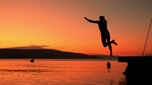 SUPER SLO MO Man jumping into the sea at dusk