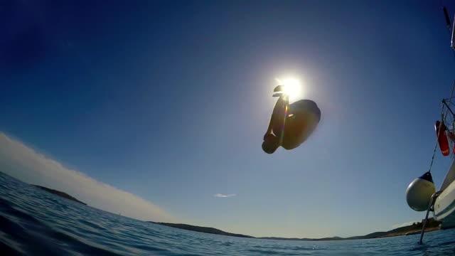 mann springt ins meer von einem segelboot - sprung wassersport stock-videos und b-roll-filmmaterial