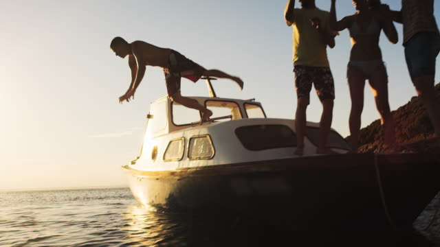 SLO MO Man jumping into the water from a party boat at sunset video