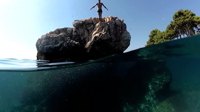 slow-motion close up unterwasser: mann springen ins wasser auf kopf von einem hohen felsen im meer - sprung wassersport stock-videos und b-roll-filmmaterial