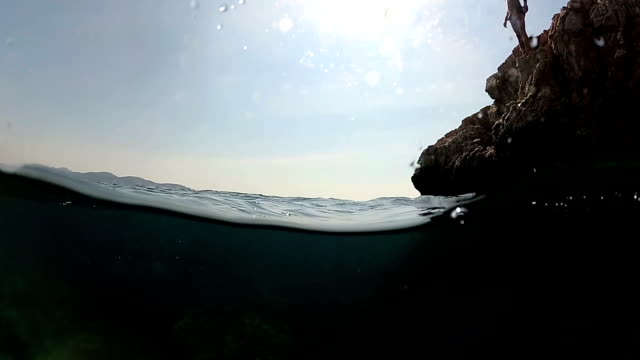 slow motion close up underwater: man jumping into water on head off a high rock in to sea - mika video stock e b–roll