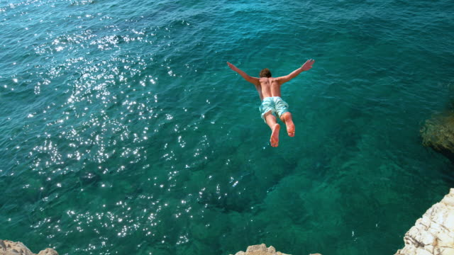 複製空間:人類跳下岩石岩壁,進入閃閃發光的藍色海洋。 - 懸崖 個影片檔及 b 捲影像