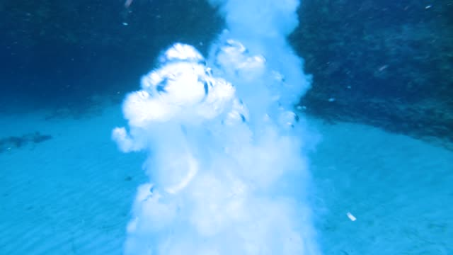 Man jumping off cliff and diving into ocean Young fearless man diving underwater into tropical island sea water after jumping off cliff cliff jumping stock videos & royalty-free footage