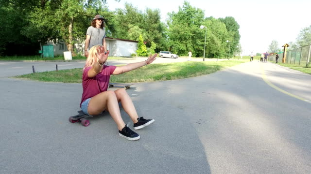 Man jumping over his female friend which is sitting on longboard video