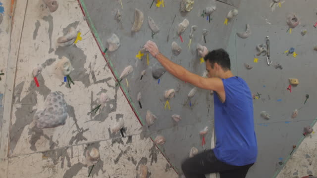 man jumping to reach a boulder at the climbing wall - inerpicarsi video stock e b–roll